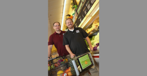 NMSU researchers Mihai Niculescu, left, and Collin Payne with a grocery cart placard used in grocery stores to study how in-store marketing can be used to influence shoppers to buy more fresh fruit and vegetables. (NMSU photo by Robert Yee)