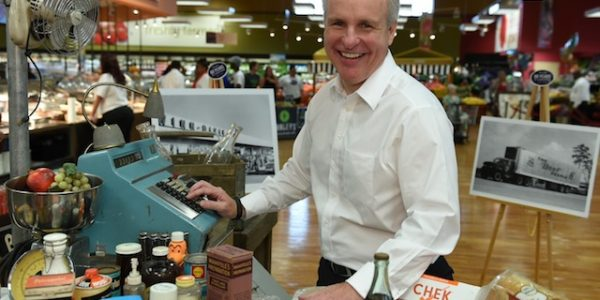 Southeastern Grocers COO Anthony Hucker poses with a 1956-themed checkout lane.