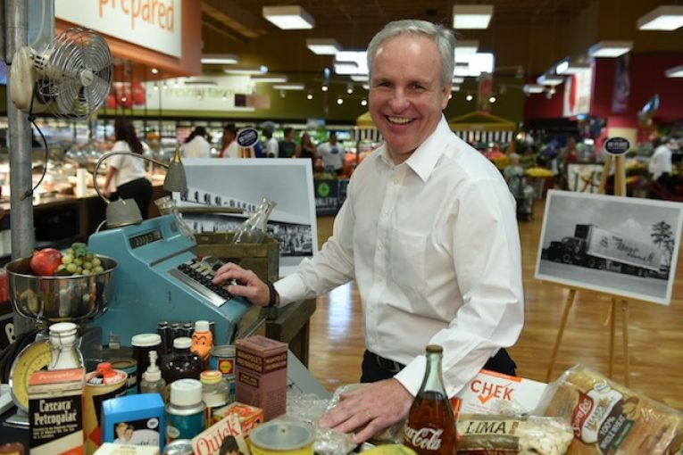 Southeastern Grocers' new president and CEO, Anthony Hucker, poses with a 1956-themed checkout lane.