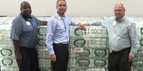 Super 1 Foods store directors Lester Washington, left, and Jay Holmes, center, along with SVP-Division Manager Gregg Skelly, right, are pictured with a portion of the water from the truckload donation to the Red Cross in Lafayette, Louisiana.