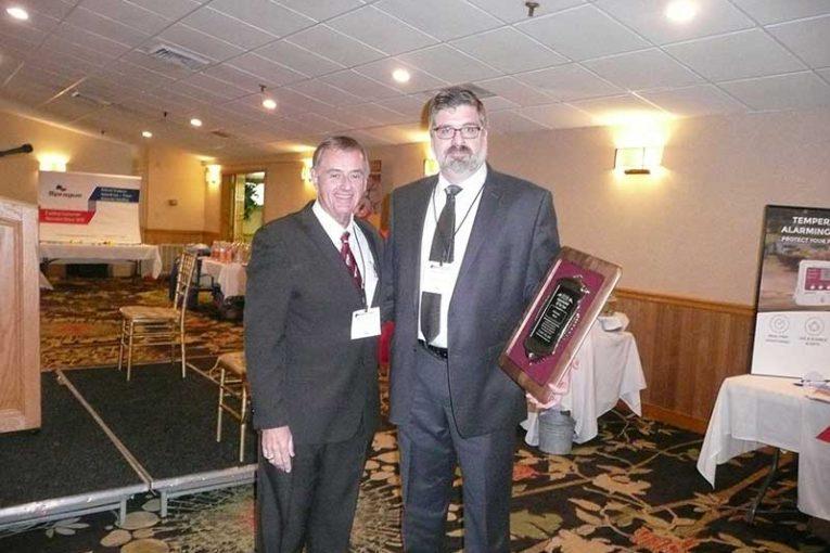 NHGA President John Dumais presents the Supermarket of the Year Award to Ed Penta of McKinnon's Market.