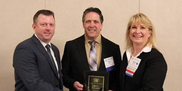 MGA Board Chair Mark Collier of Superfair Foods presents Mike Oase of Kowalski's Cos. with the 2017 Best in Class-Retail Award alongside MGA President Jamie Pfuhl.