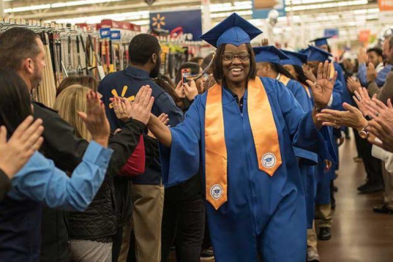 A Walmart associate receives high-fives as she enters an academy graduation.