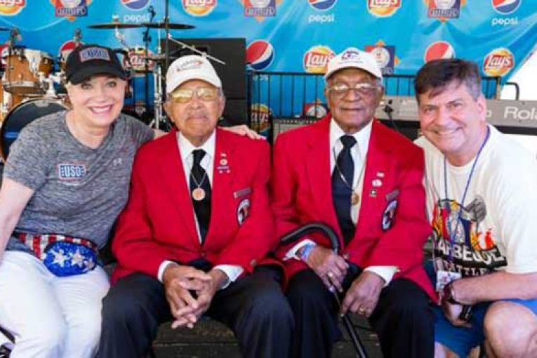 Elaine Rogers, president of USO of Metropolitan Washington-Baltimore, and Gordon Reid, president of Giant Food of Landover, right, celebrate the opening of the 25th Annual Giant National Capital Barbecue Battle with Walter Robinson Jr. and William Fauntroy Jr., two Tuskegee Airmen who served during World War II.