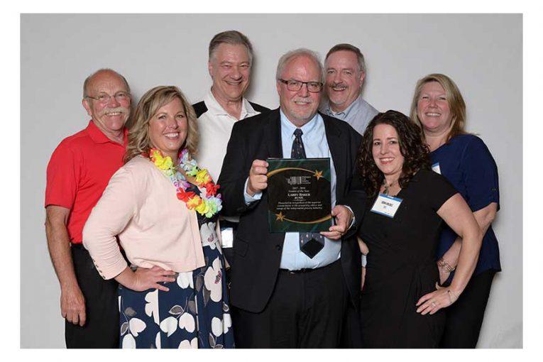 Larrry Baker, center, celebrates his Vendor of the Year award with fellow Bunzl employees Rick Sorenson, Shannon Parker, Bob Hensen, Mike Barhart, Trina Valdez and Lisa McNeeley. (Photo © 2018 CJ Photo NW)