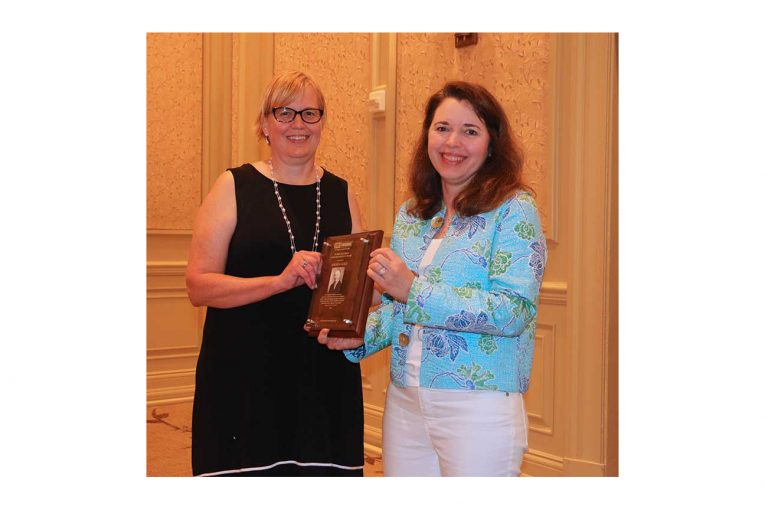 Andrea Gold accepting the award from FMI's Jennifer Hatcher.
