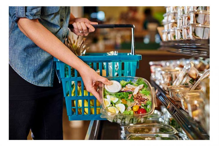A woman picking up a prepared salad from a cold case