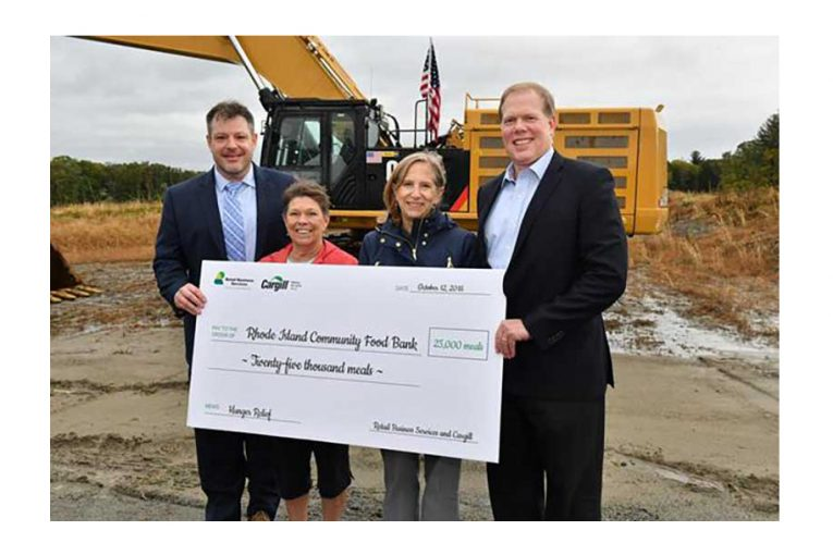 Four people at the groundbreaking ceremony hold a large check.