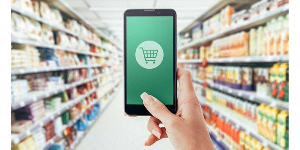A phone with an image of a shopping backset in the foreground and grocery aisles in the background.