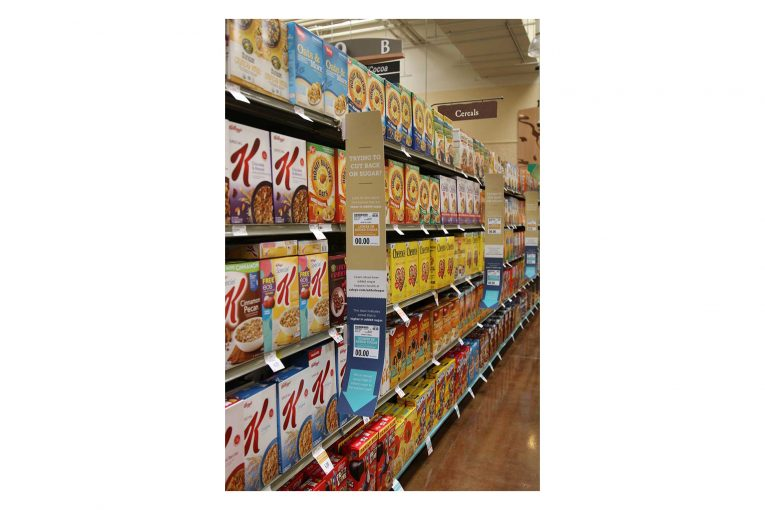 A Raley's cereal aisle with shelf blades explaining the new product placement.