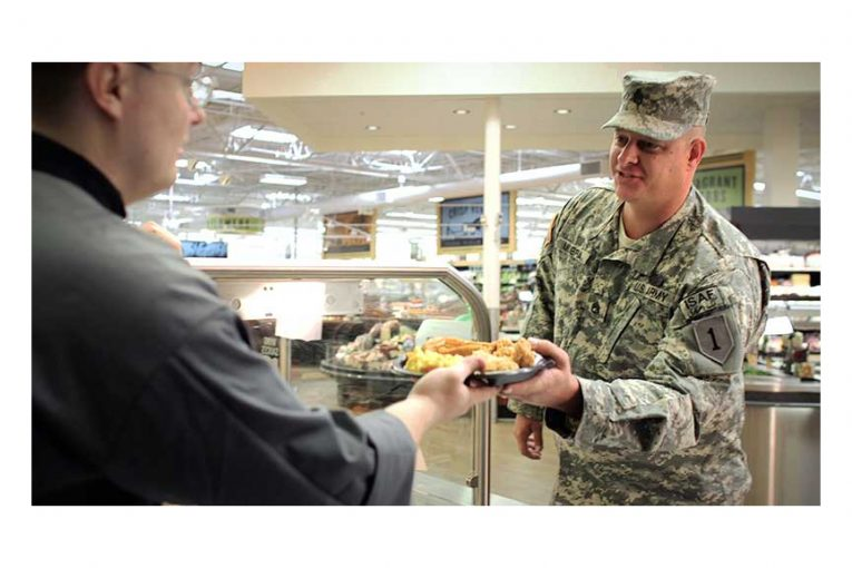 A Reasor's employee hands a plate of food to a man in a military uniform.