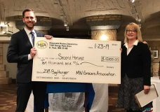 Pfuhl presents Marcus Schmit of Second Harvest Heartland with a donation on behalf of the 2018 Bag Hunger Campaign.
